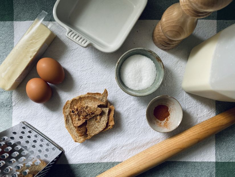 Ingredients for a recipe, including eggs, butter, salt, and some utensils