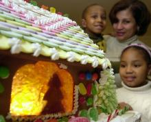 Photograph of people looking at a gingerbread house