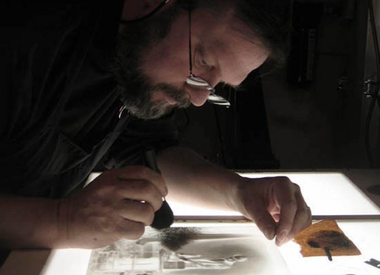 Mark retouching a glass plate photograph